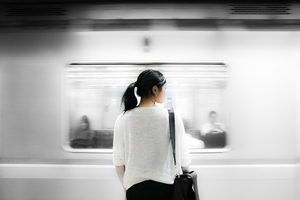 Entrepreneur woman watching subway go by while she stays